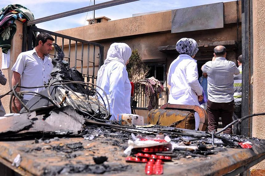 People inspect the damage in the Maysalun clinic where a fire broke out after a fuel tank exploded on May 31, 2015 in the north-eastern city of Qamishli. The fire on Sunday killed 27 people, mostly children, and injured about 30 others, official medi