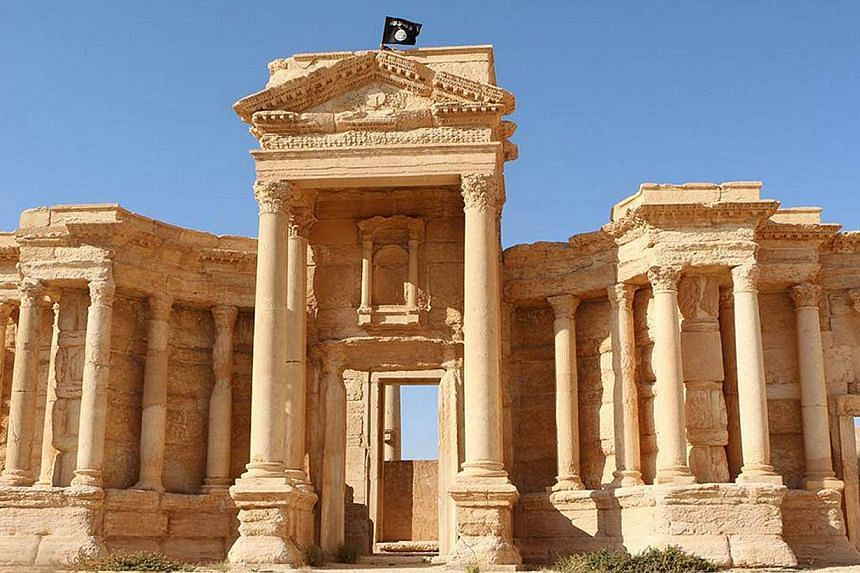 An image made available by Jihadist media outlet Welayat Homs on May 28, 2015 allegedly shows a flag of the Islamic State in Iraq and Syria (ISIS) on the circular wall bounding the Roman theatre of the ancient city of Palmyra.The anti-ISIS coal