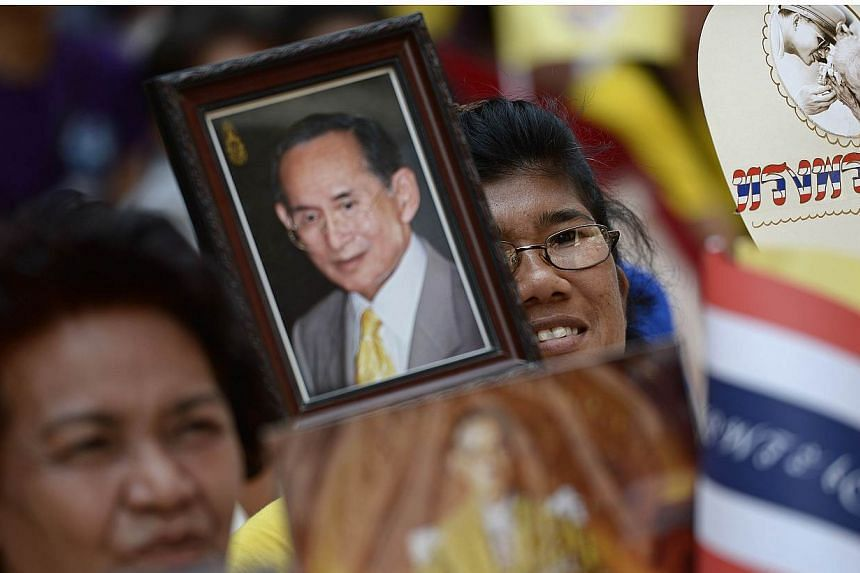 Well-wishers hold portraits of Thai King Bhumibol Adulyadej and wave national flags as they line up the streets outside the Siriraj hospital in Bangkok on May 10, 2015.Thailand's revered but ailing king has returned to hospital in Bangkok for m