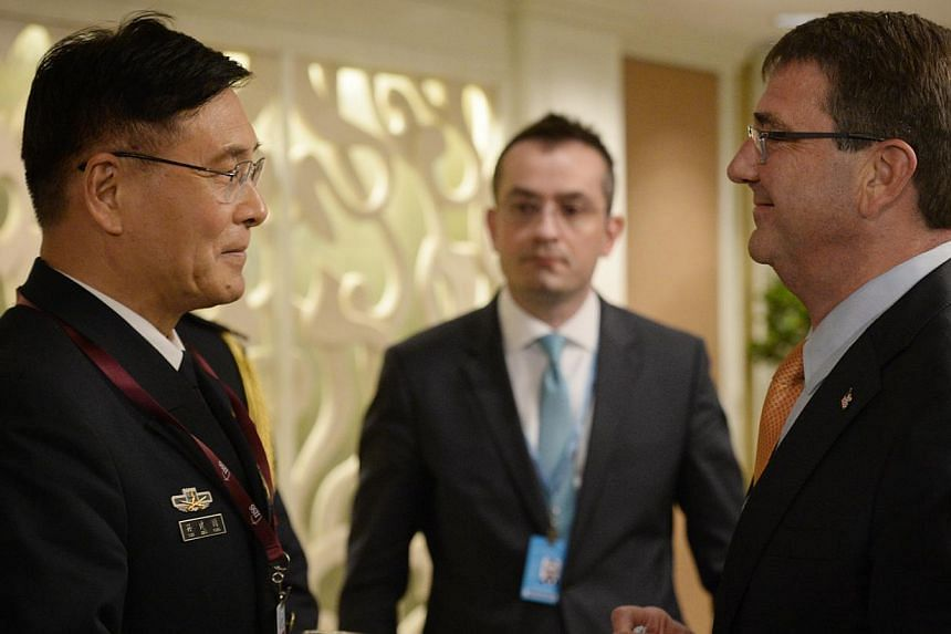 Chinese Deputy Chief, General Staff Department, People's Liberation Army, Admiral Sun Jianguo (left) speaks to United States Secretary of Defense Dr Ashton Carter during the Ministerial Luncheon during the IISS Shangri-La Dialogue on May 31, 2015. --