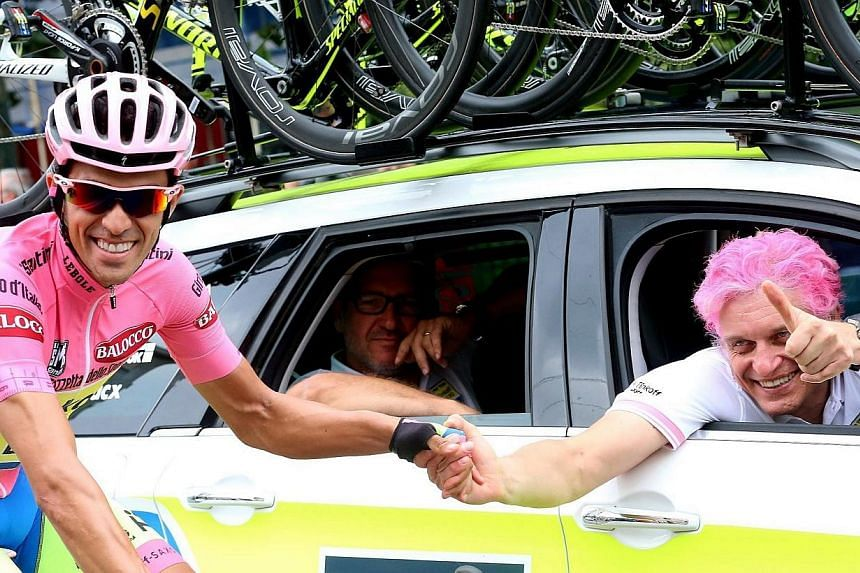 Spanish rider Alberto Contador (left) of the Tinkoff-Saxo team and Russian businessman and team owner Oleg Tinkov,  with his hair painted in pink to match the overall leader's jersey, on the way to the 21st and last stage of the 98th Giro d