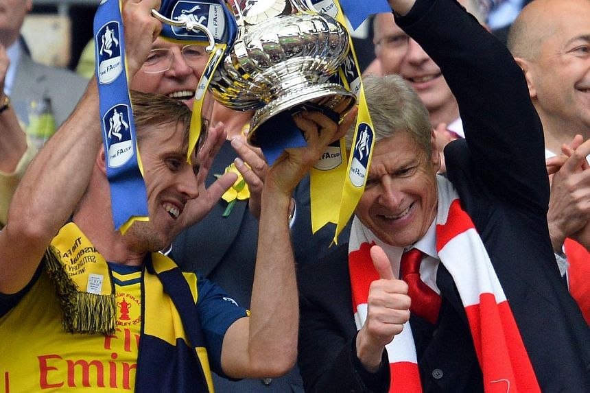 Arsenal manager Arsene Wenger (right) holding aloft the FA Cup trophy with defender Nacho Monreal after his team demolished Aston Villa 4-0 in the final at Wembley, London, on May 30, 2015. -- PHOTO: AFP