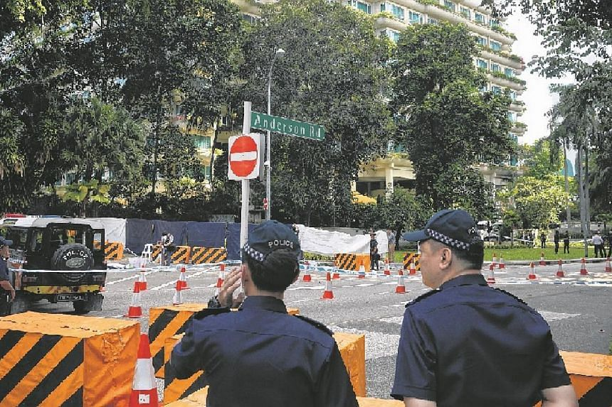 Members of the Singapore Police Force stand around a cordoned area at the junction of Orange Grove Road and Anderson Road where an early morning shooting incident occurred on May 31, 2015. A man identified as Mohamad Taufik Zahar was shot dead and tw