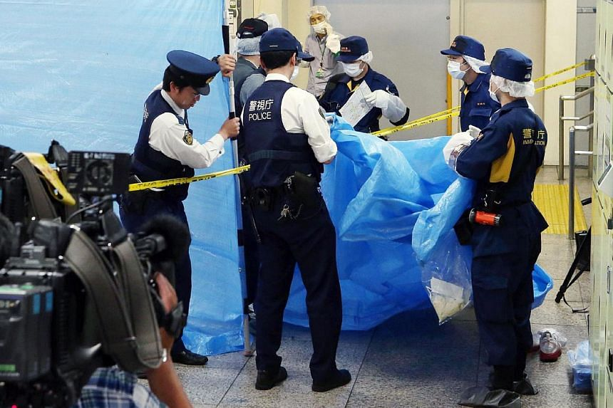 This photograph taken on May 31, 2015 shows police officers inspecting a locker at the Tokyo station. -- PHOTO: AFP