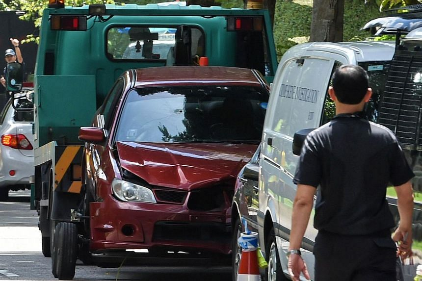 A damaged red car with a bullet hole on its windscreen is being towed away in Singapore near the Shangri-La hotel on May 31, 2015. Two passengers in the car that crashed through police barriers near the Shangri-la Hotel in the wee hours of Sunday wer