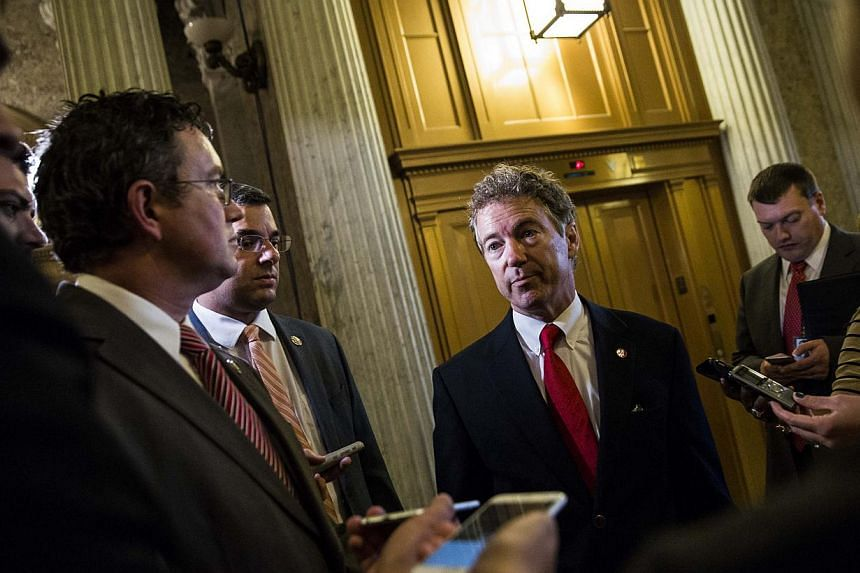 Senator Rand Paul (centre), after speaking on the Senate floor about surveillance legislation, speaks to reporters after exiting the Senate floor on Capitol Hill, Washington, DC, on May 31, 2015. -- PHOTO: AFP