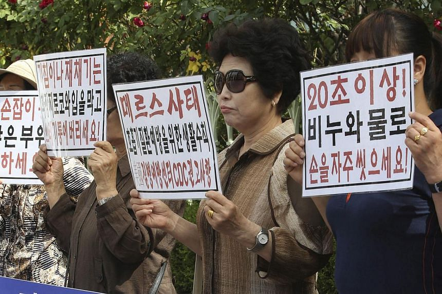 Members of a civic group on public health rally in front of the state-run National Health Insurance Service in Seoul, South Korea, on June 1, 2015, to urge the government to release information on places of residence related to patients infected with
