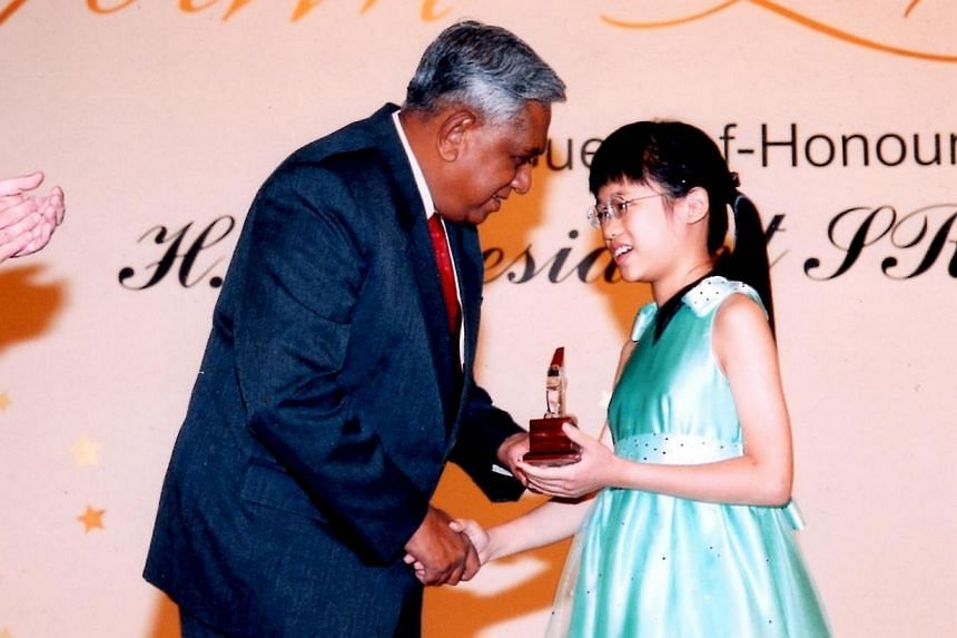 Abigail Sin at age four with her twin Josiah, younger brother David and father Sin Lye Kuen. Abigail Sin at age 11, receiving the HSBC Youth Excellence Award from then President S R Nathan. Abigail Sin at age eight in Methodist Girls' School.