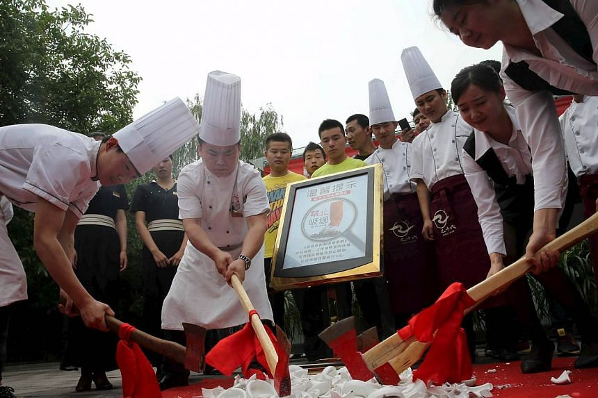 Restaurant staff axe ashtrays as Beijing started new anti-smoking curb, China, on June 1, 2015.China's capital city was sprinkled with red-uniformed volunteers, propaganda banners and no-smoking signs on Monday as Beijing unrolled ambitious new
