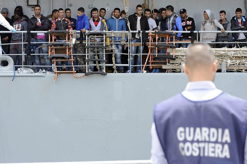 Migrants wait to disembark from the Irish navy ship LE Eithne as they arrives in the Sicilian harbour of Palermo, Italy, on May 30, 2015.European powerhouses France and Germany on Monday, June 1, called on the EU to revise its plan to admit asy