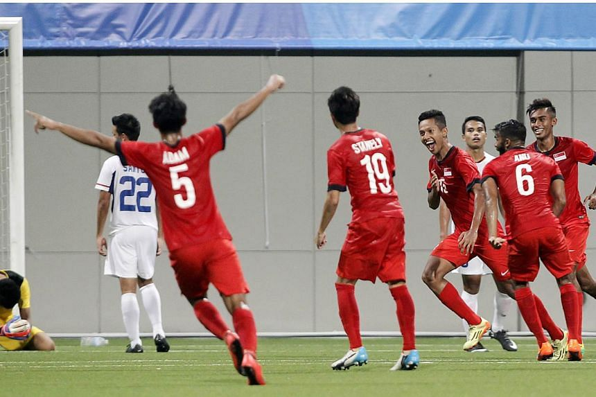 Singapore's Sheikh Abdul Hadi (fourth right) celebrates after scoring the match's only goal. -- PHOTO: REUTERS