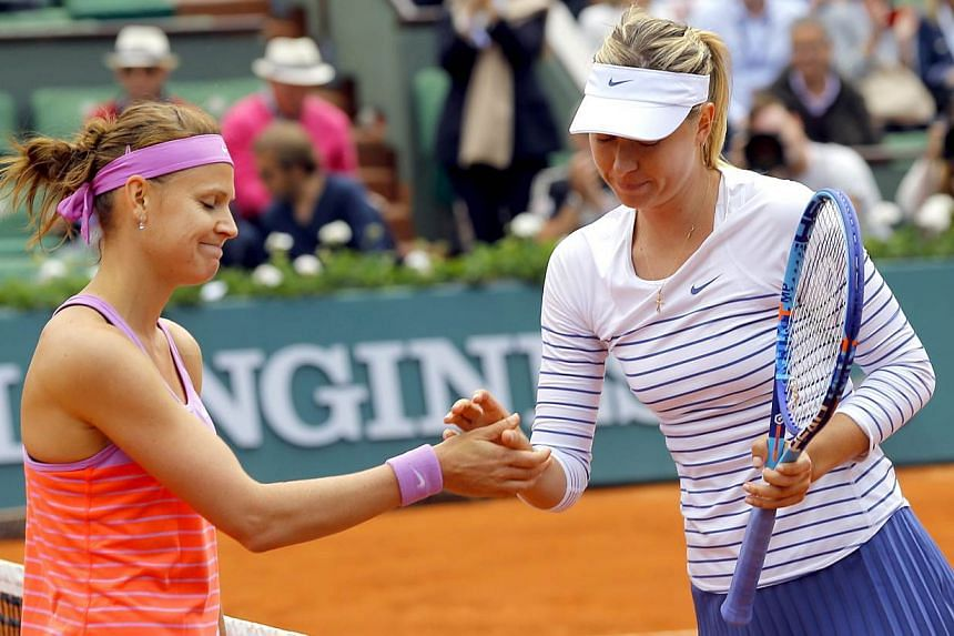 Lucie Safarova of Czech Republilc (left) shakes hands after winning against Maria Sharapova of Russia during their fourth round match for the French Open tennis tournament at Roland Garros in Paris, France on June 1, 2015. -- PHOTO: EPA