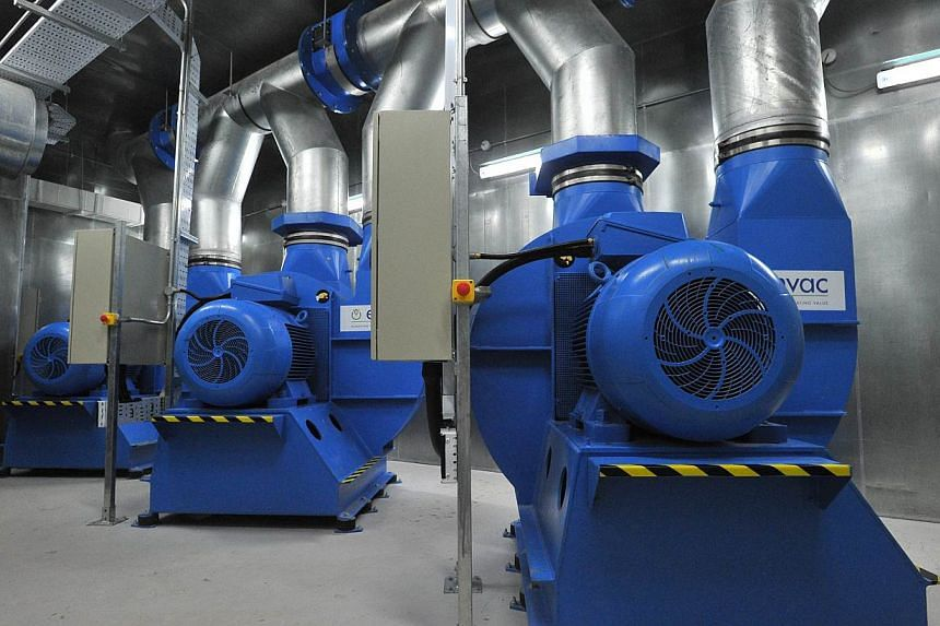 The Exhaustor, part of the new pneumatic waste collection system being tested on several HDB block in Yuhua, is a centrifugal pump that creates suction, in the centralised bin centre on May 28, 2015. -- ST PHOTO: LIM YAOHUI FOR THE STRAITS TIMES
