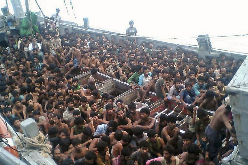 A handout picture released by the Myanmar Ministry of Information on May 30, 2015 shows migrants who were seized by the Myanmar navy in a boat near the Irrawaddy delta on May 29, 2015. The migrants were still being held offshore by Myanmar's nav