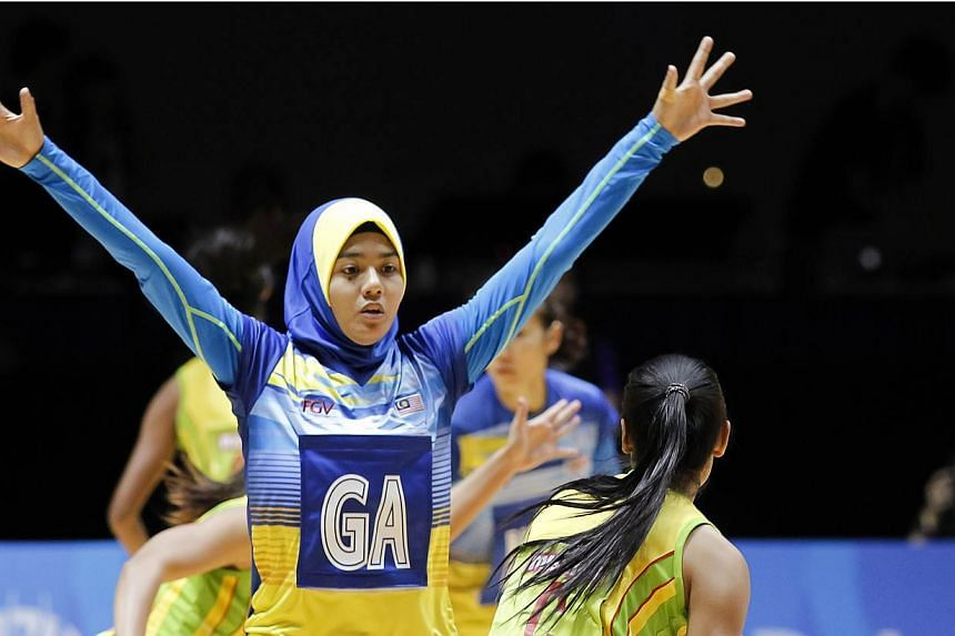 Malaysia's netballer Izyan Syazana Mohd Wazir (left) in action at the SEA Games 2015. Defending SEA Games netball champion Malaysia sent out a statement of intent to the other teams with a ruthless 112-11 thrashing of the Philippines on June 1, 2015