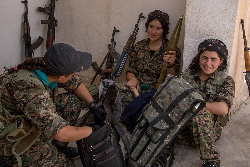 Armed Kurdish female fighters from People's Protection Units (YPG) talk to each other in the Assyrian village of Tel Nasri, western of Tel Tamr town, after the YPG said they retook control of the area from ISIS. -- PHOTO:REUTERS