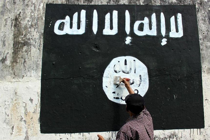 A resident painting over an ISIS flag in Solo, Central Java. The Islamic State in Iraq and Syria (ISIS) has ramped up its activities in South-east Asia so effectively that there is now an entire military unit of terrorists recruited from Indonesia, M
