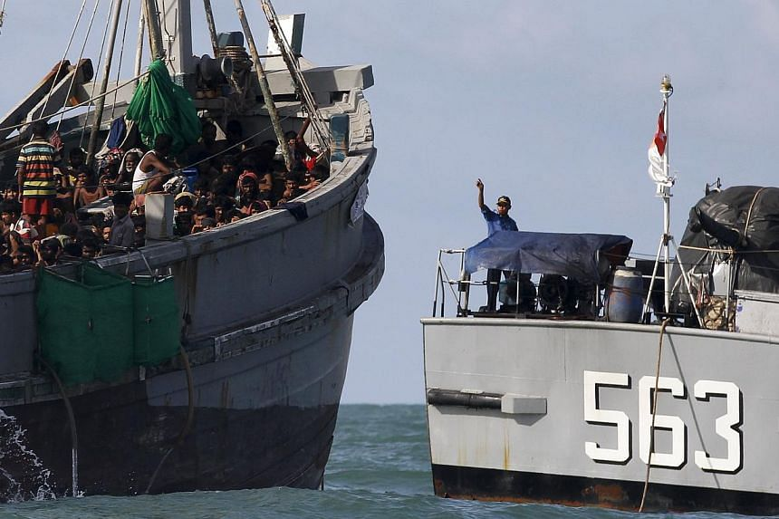 A Myanmar military officer (right) gestures from a navy ship towards a boat packed with migrants, off Leik Island in the Andaman Sea onMay 31, 2015. Myanmar's navy is escorting a boat crammed with 727 abandoned migrants to the waters of neighbo