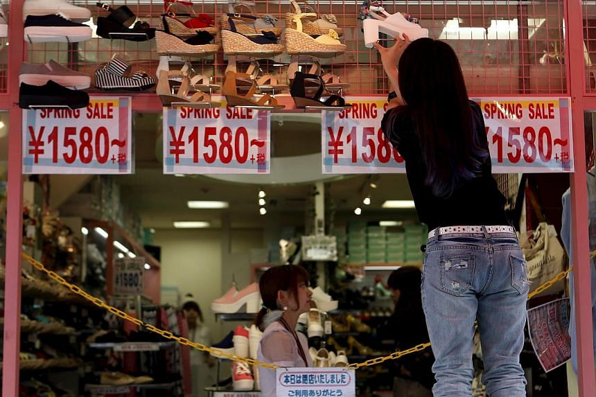 A worker preparing to open a shoe store in Tokyo's Harajuku shopping district on April 30, 2015. Japan's inflation-adjusted real wages in April turned positive for the first time in two years, adding steam to Tokyo's hope that higher pay will spur co