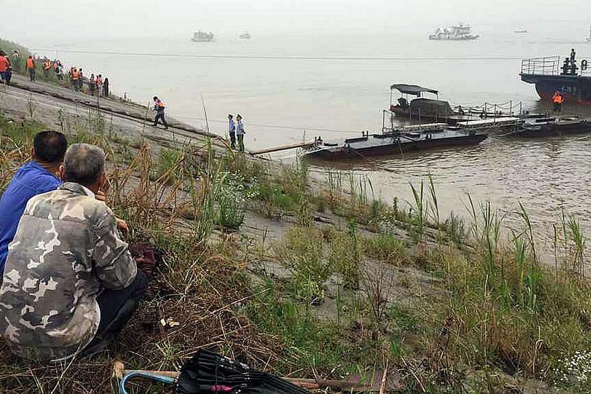 Chinese villagers watching as rescue teams head out to search for survivors of a passenger ship carrying more than 450 people which sunk in the Yangtze river, triggering a rescue effort hampered by strong winds and heavy rain off Jianli in China's Hu