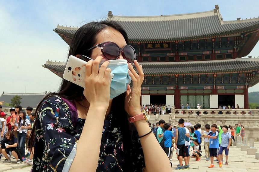 A Chinese tourist wearing a mask to prevent contracting Middle East Respiratory Syndrome (MERS) tours the Gyeongbok Palace in Seoul, South Korea, on June 1, 2015. -- PHOTO: REUTERS