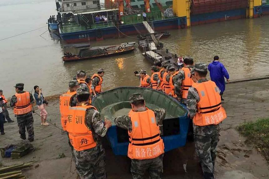Rescue workers carrying a boat to conduct a search after a ship sank at the Jianli section of Yangtze River, Hubei province, on June 2, 2015. -- PHOTO: REUTERS