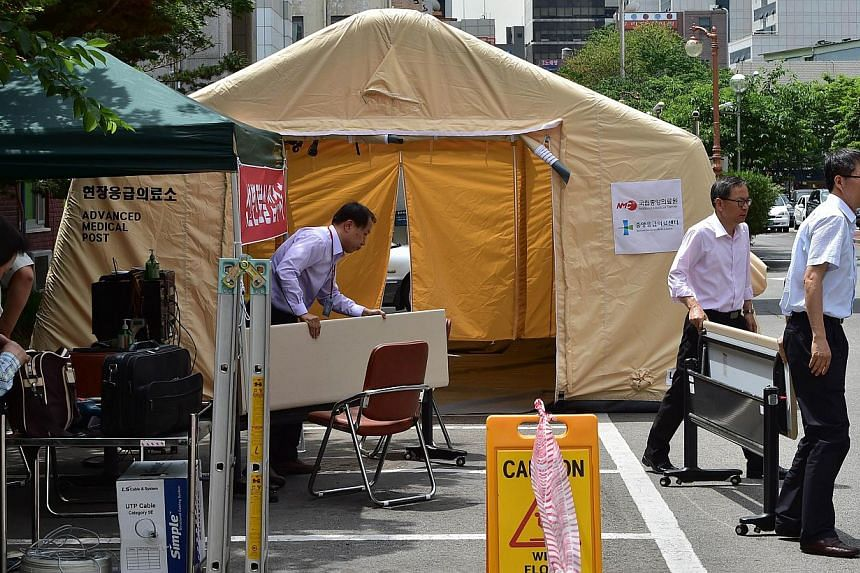 South Korean hospital workers settting up a separate emergency centre for Mers cases at the National Medical Center in Seoul on June 1, 2015. The country's health ministry confirmed on Tuesday that two people had died from the virus. -- PHOTO: AFP&nb