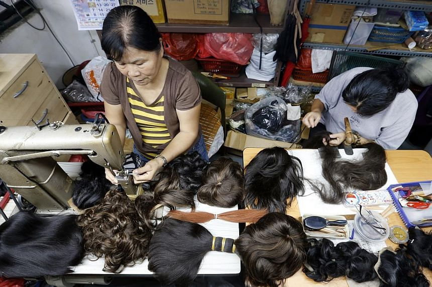 Workers at Singapura Hair Wigs making wigs that will be loaned to cancer patients. It was commissioned by Tan Tock Seng Hospital to make wigs from donated hair - nearly 120 people have pledged their hair.