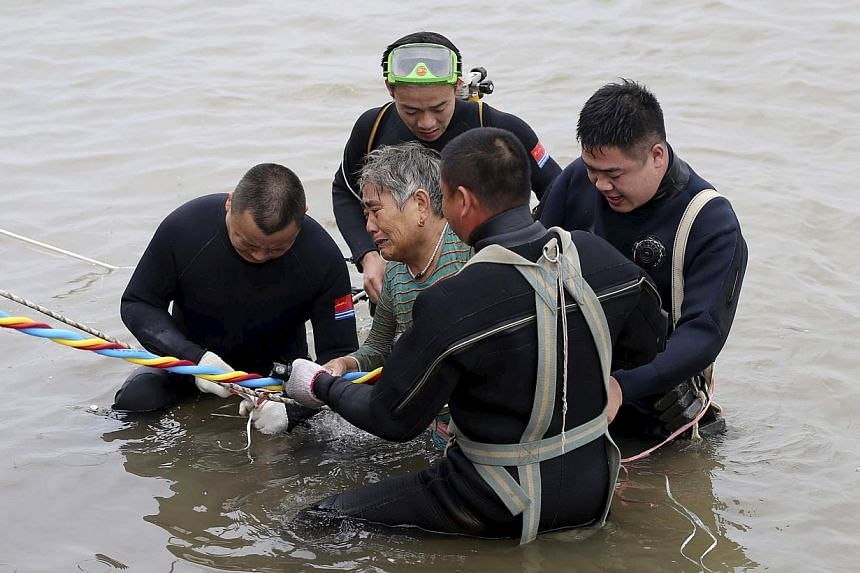 A woman is helped after being pulled out by divers from a capsized ship in Jianli, Hubei province, China on June 2, 2015. Rescuers are working to save five more passengers trapped inside the hull of the ship that capsized in China's Yangtze River&nbs