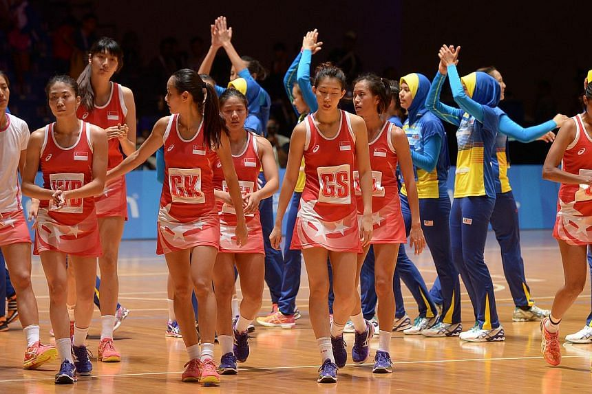 The Singapore team disconsolately walked back to their bench after the match. The hosts let a six-point lead slip in the fourth quarter against Malaysia. -- ST PHOTO: DESMOND WEE