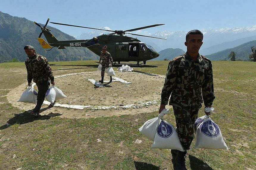 Nepalese Army soldiers run with parcels of food aid unloaded from a military transport helicopter at an army camp in the village of Rasuwa on May 28, 2015. Ahelicopter which had been delivering relief supplies crashed in Nepal's Sindhupalchowk