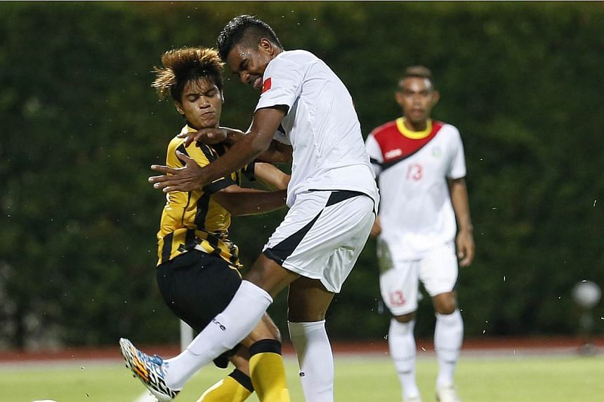 Malaysia's Muhammad Nazmi Faiz Mansor (left) collides with Timor Leste's Filipe Oliveira during one of their few notable altercations in the 28th SEA Games men's football first round group B match at the Bishan Stadium on May 30, 2015. Nazmi has