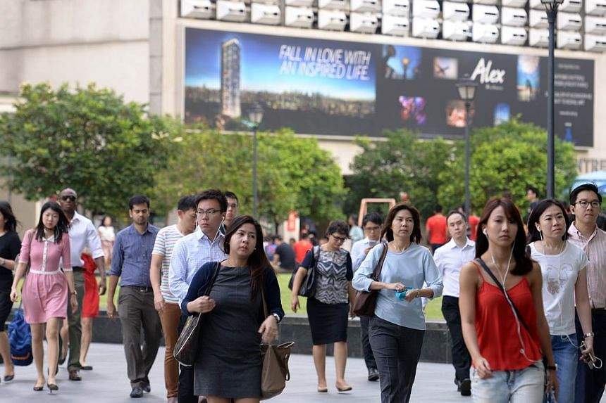 Office workers at Raffles Place on Feb 18, 2015. Employees in Singapore could see their salaries grow by 4.4 per cent this year, on the back of low inflation, according to a survey released on Tuesday. -- ST PHOTO: DANIEL NEO