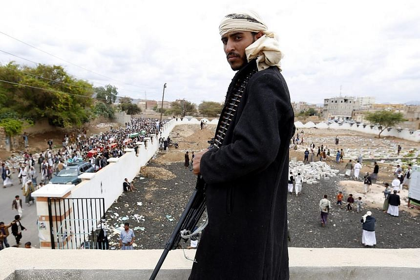 A member of Houthi militia looks on as Houthi supporters carry the coffins of comrades killed allegedly in an airstrike carried out by the Saudi-led coalition on a Houthi position in Sana'a, Yemen, -- PHOTO: EPA