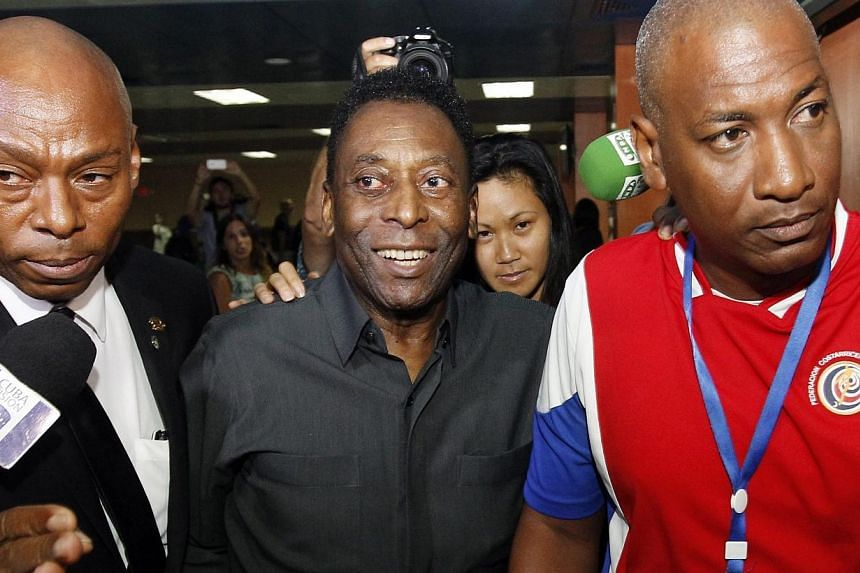 Former football superstar Edson Arantes do Nascimiento Pele (centre) arrives in Havana, Cuba on Sunday (May 31) where he told journalists that he supports the re-election of Joseph Blatter as president of FIFA. -- PHOTO: EPA