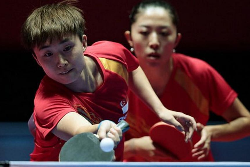 Singapore paddlers Feng Tianwei (left) and Yu Mengyu in action during the SEA Games' women's doubles competition at the Singapore Indoor Stadium on June 1, 2015. -- PHOTO: REUTERS