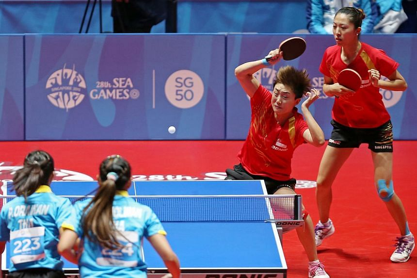 Singapore paddlers Yu Mengyu (far right) and Feng Tianwei in action against Thailand in the SEA Games women's doubles quarter-finals at the Singapore Indoor Stadium on June 1, 2015. -- ST PHOTO: SEAH KWANG PENG