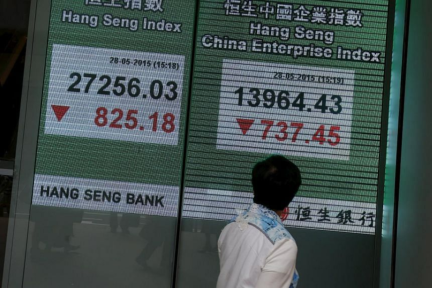 A passerby looking at a panel displaying the blue-chip Hang Seng Index outside a bank during afternoon trading in Hong Kong, China on May 28, 2015. -- PHOTO: REUTERS