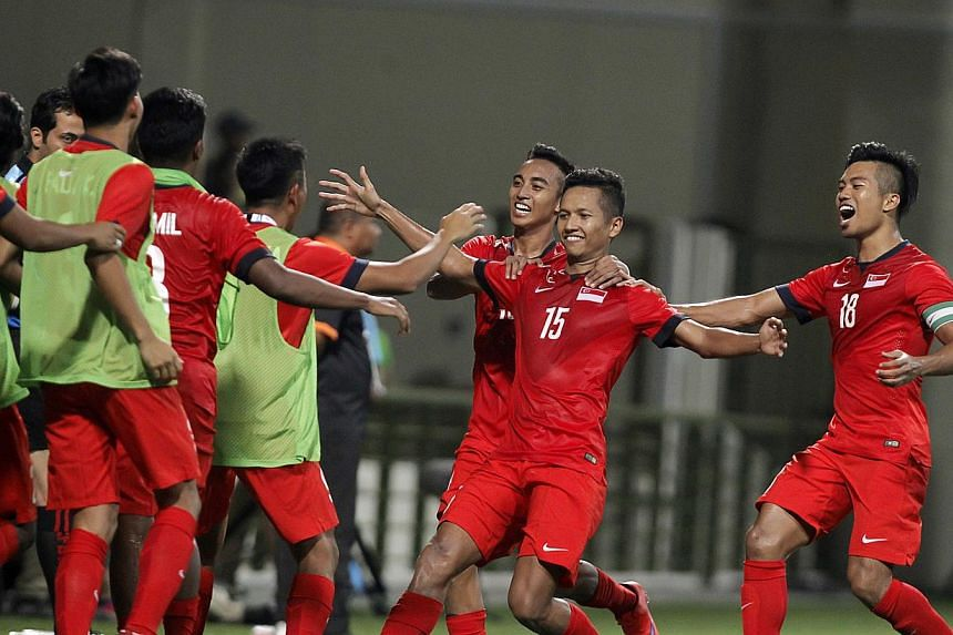 Singapore's under-23 defender Sheikh Abdul Hadi Sh Othman (No.15) celebrating with his teammates after scoring the goal against the Philippines at the 28th Sea Games held at the Jalan Besar Stadium on June 1, 2015. Singapore's coach Aide Is