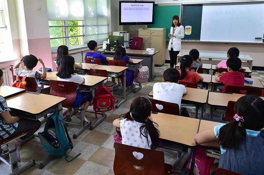 South Korean school students attending a special class on Mers virus at an elementary school in Seoul on June 3, 2015. -- PHOTO: AFP