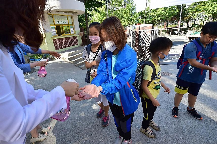 South Korean school workers spraying sanitiser on hands of students to protect against possible Mers virus at an elementary school in Seoul on June 3, 2015. -- PHOTO: AFP
