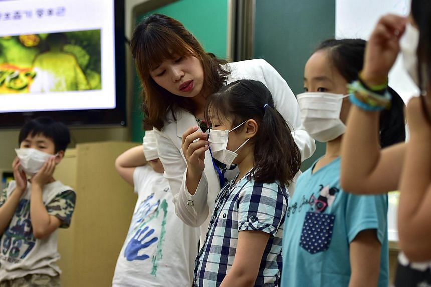 South Korean school students putting on face masks during a special class on Mers virus at an elementary school in Seoul on June 3, 2015. -- PHOTO: AFP