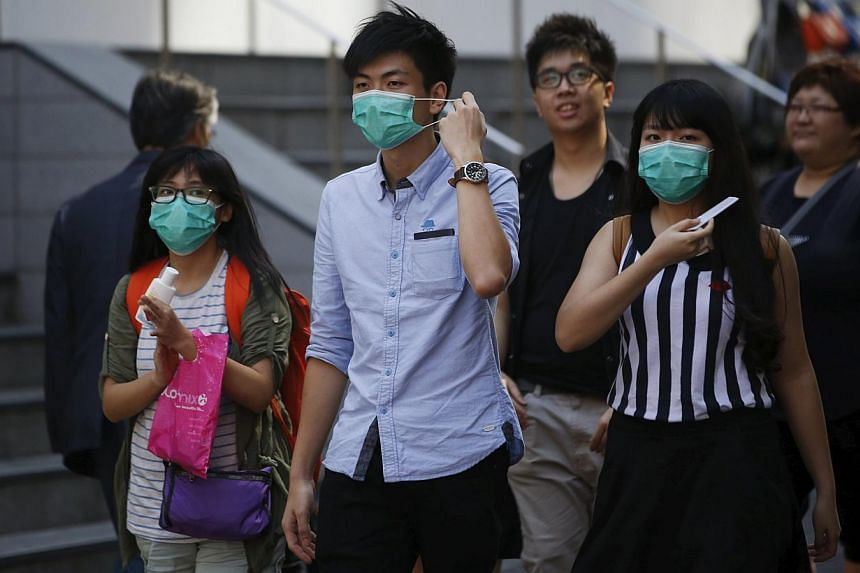 Tourists wearing masks to prevent contracting Middle East Respiratory Syndrome (Mers), walk at Myeongdong shopping district in central Seoul, South Korea on June 3, 2015. -- PHOTO: REUTERS