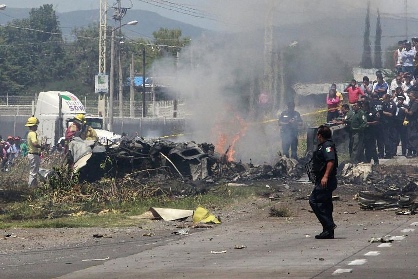 Mexican firefighters and members of Mexican Federal Police inspecting the site where a small plane crashed on the highway between Mexico City and Queretaro, Mexico, on June 2, 2015. -- PHOTO: EPA