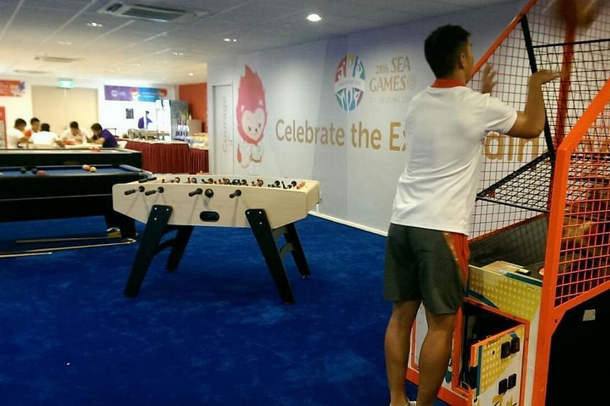 Singapore rugby player Samuel Teo trying out the basketball machine in the Nila Suite. -- ST PHOTO: HO SI RUI