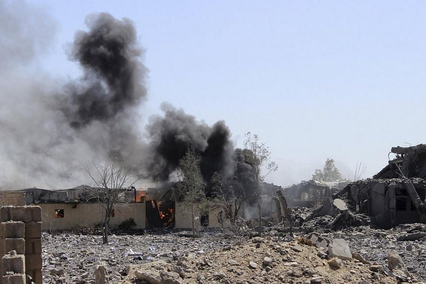 Smoke billowing from a storage building belonging to the education ministry's printing press corporation after it was hit by a Saudi-led air strike in Yemen's north-western city of Saada on June 2, 2015. -- PHOTO: REUTERS