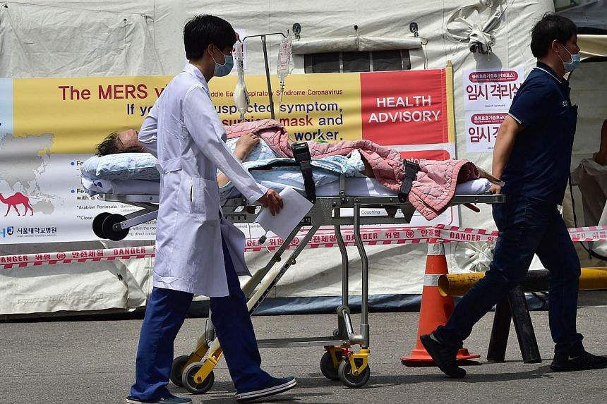 South Korean hospital workers wheeling a man in front of a quarantine tent for suspected Mers cases at the Seoul National University Hospital in Seoul on June 2, 2015. -- PHOTO: AFP