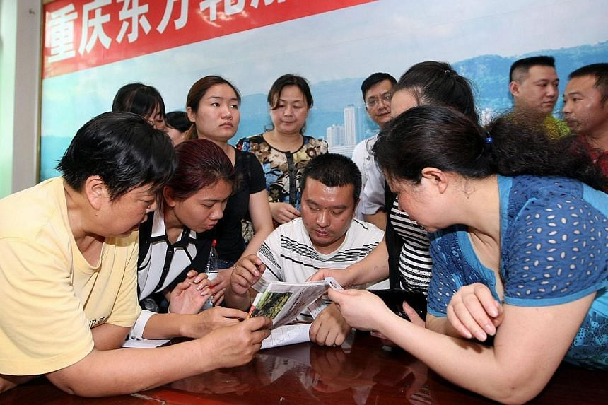 "This photograph taken on June 2, 2015 shows relatives of passengers on board the doomed vessel Dongfangzhixing or ""Eastern Star"" registering in preparation to head to the scene of the accident, at the Chongqing Wanzhou Eastern shipping company in Cho"