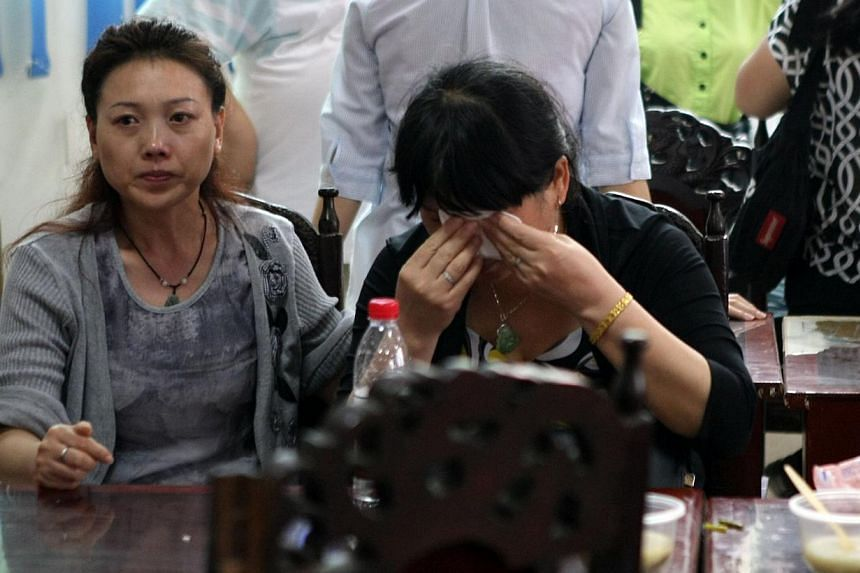 "This photograph taken on June 2, 2015 shows relatives of passengers on board the doomed vessel Dongfangzhixing or ""Eastern Star"" mourning as they wait to register in preparation to head to the scene of the accident, at the Chongqing Wanzhou Eastern s"