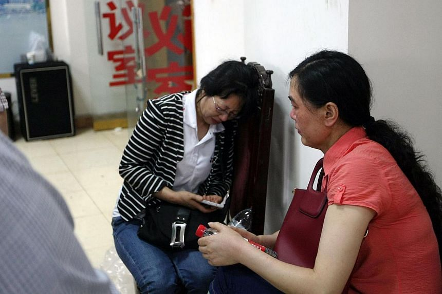 "This photograph taken on June 2, 2015 shows relatives of passengers on board the doomed vessel Dongfangzhixing or ""Eastern Star"" waiting to register in preparation to head to the scene of the accident, at the Chongqing Wanzhou Eastern shipping compan"